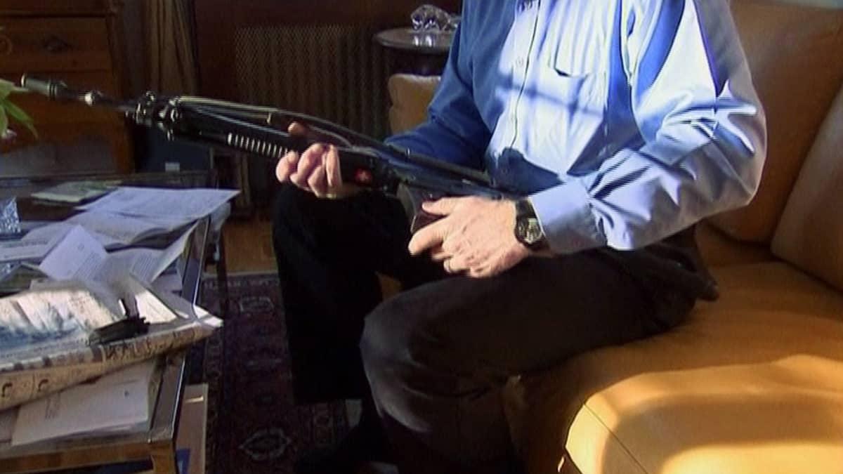 Mies istuu sohvalla rynnäkkökiväärin kanssa.
