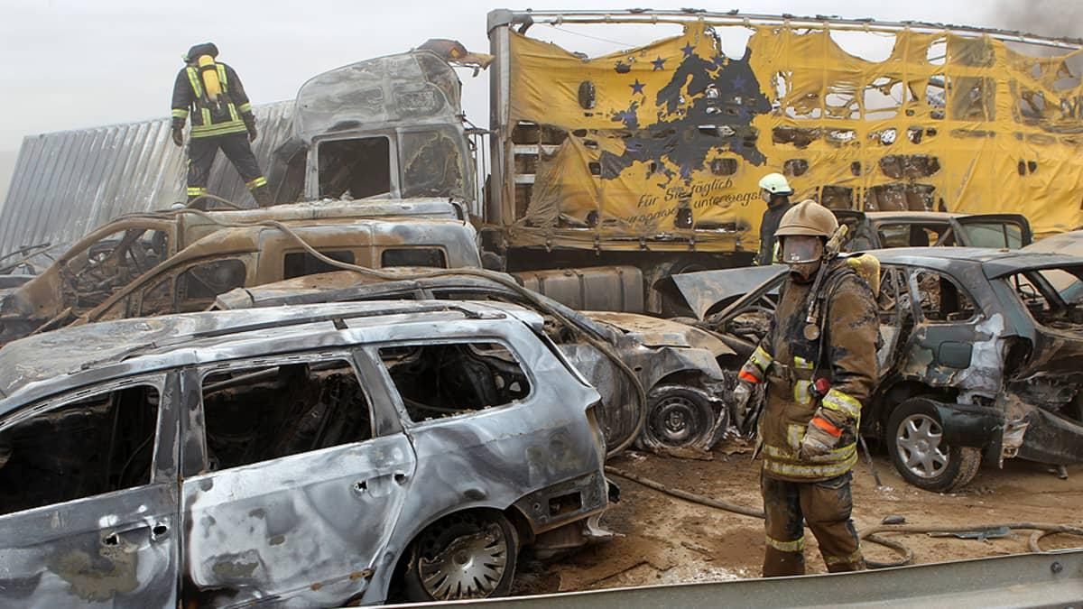 Palomiehet raivaavat moottoritiellä sattuneen ketjukolarin jälkiä.