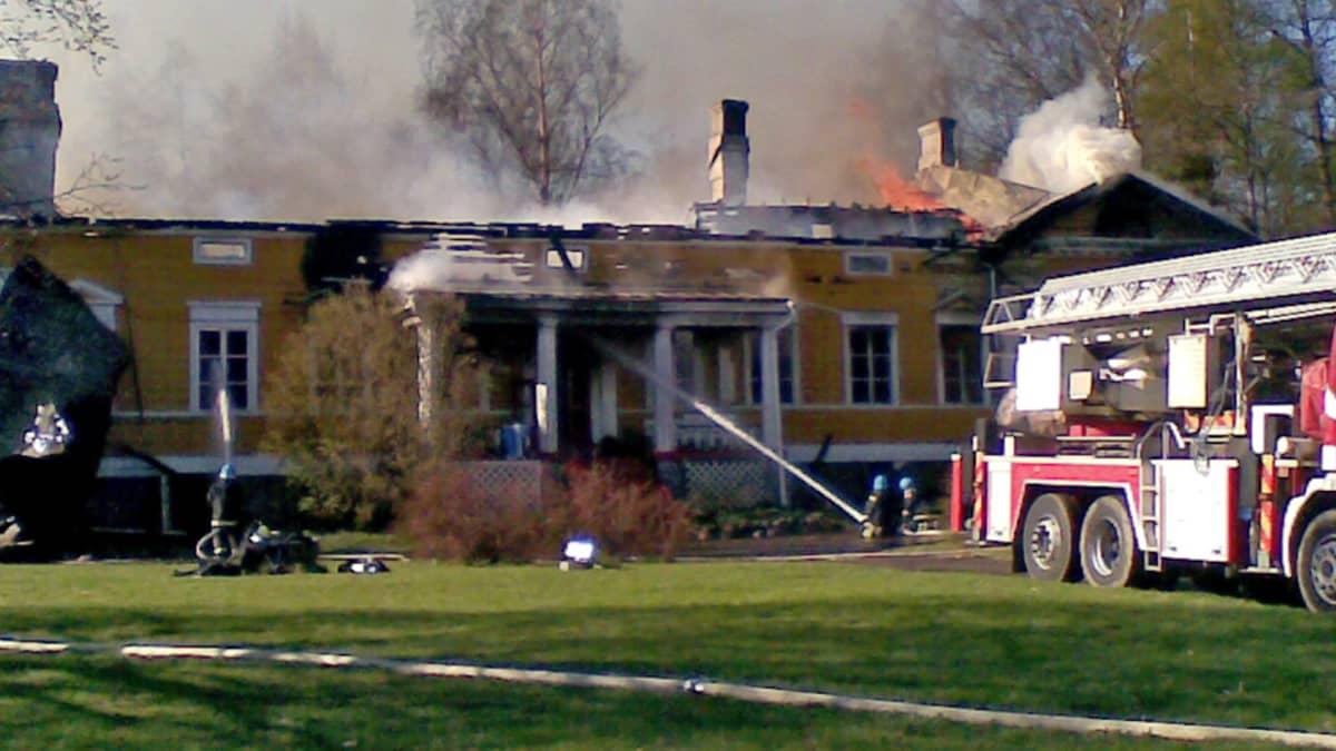 Pelastuslaitos on saapunut sammuttamaan tulipaloa äitienpäivänä. Yläosa rakennuksesta on jo tuhoutunut pahoin.