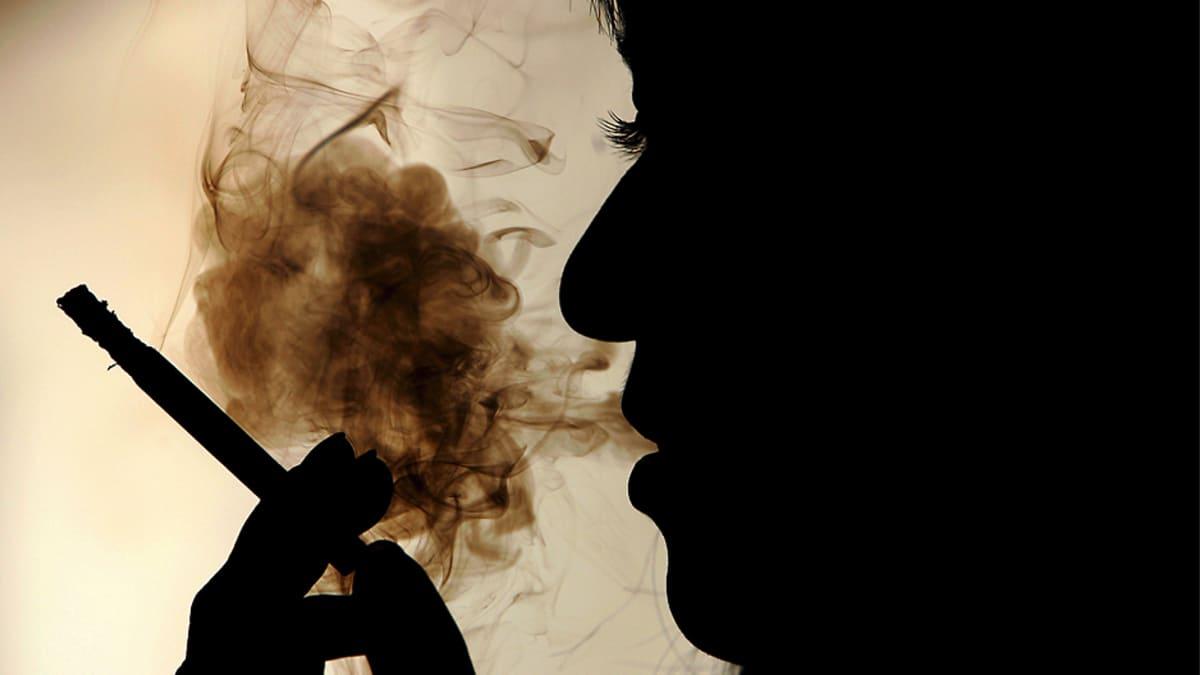 Nuori nainen polttaa tupakkaa siluetissa.