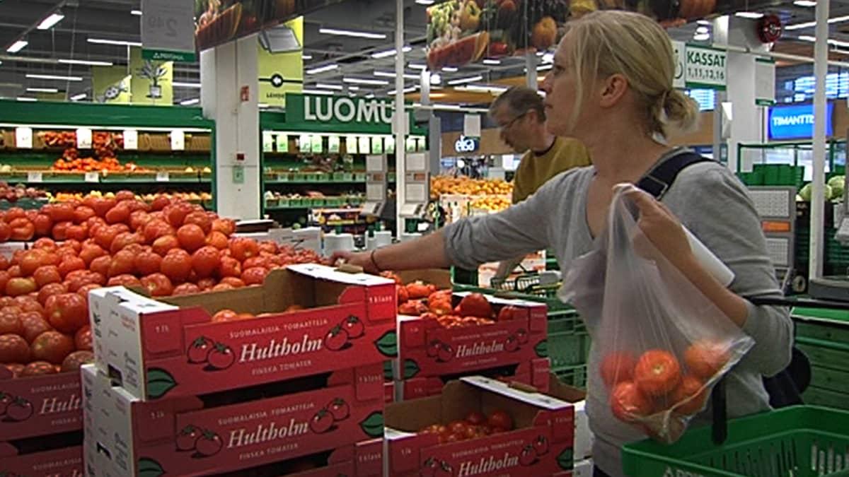 Nainen poimii kaupassa tomaatteja pussiinsa.