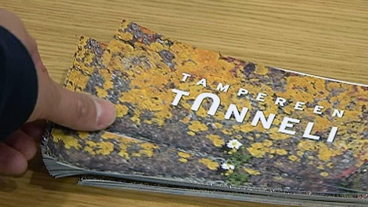 Mies ottaa Tampereen tunneli -esitettä pöydältä