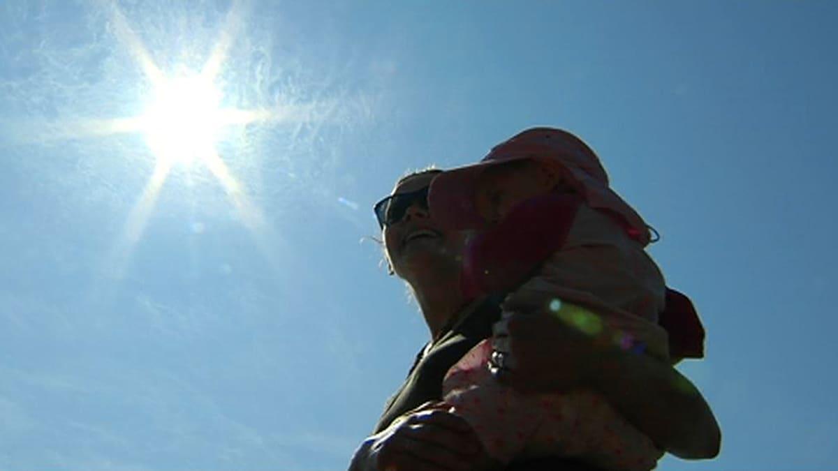 Äiti lapsensa kanssa auringossa.