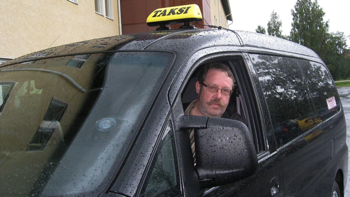 Taksimies katsoo ajokkinsa ikkunasta