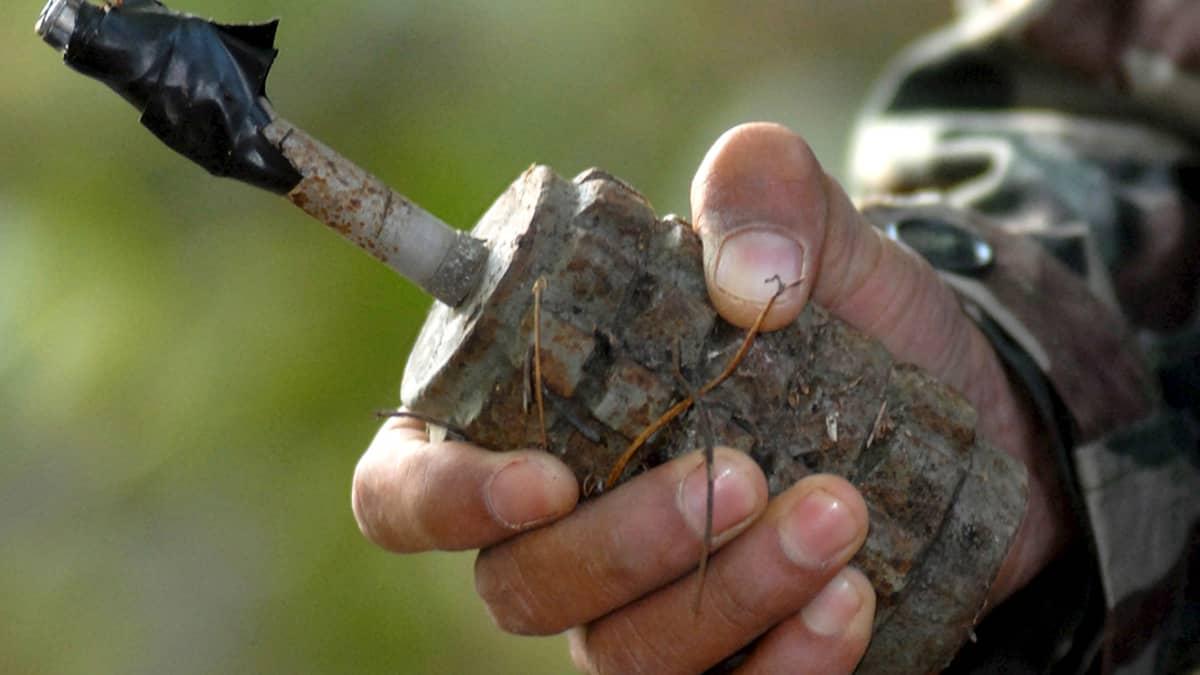 Nepalilainen miinanraivaaja pitelee sirpalemiinaa.