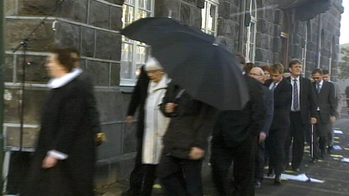 Kansanedustajat suojautuvat mielenosoittajien heittelemiltä kananmunilta muun muassa sateenvarjoin.