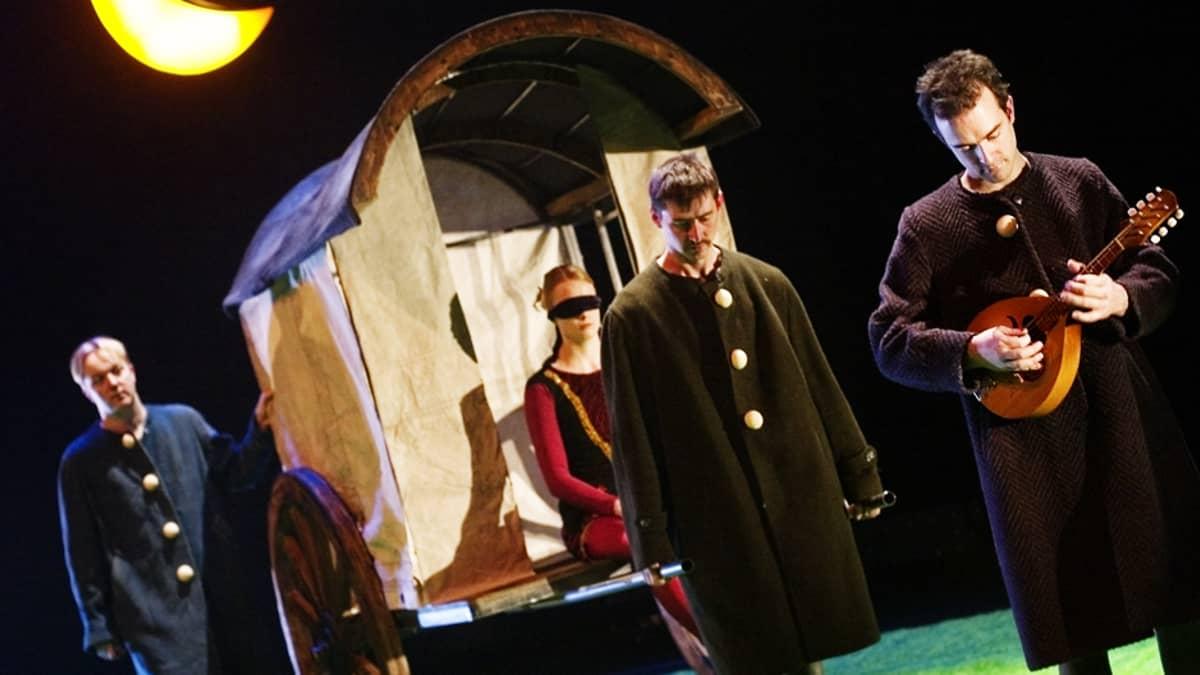 Näyttelijät lavalla. Kolme miestä seisoo ja nainen, jonka silmät on sidottu, istuu vankkurissa.