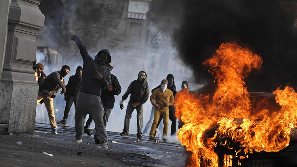Mielenosoittajat heittelevät mellakkapoliiseja kivillä.