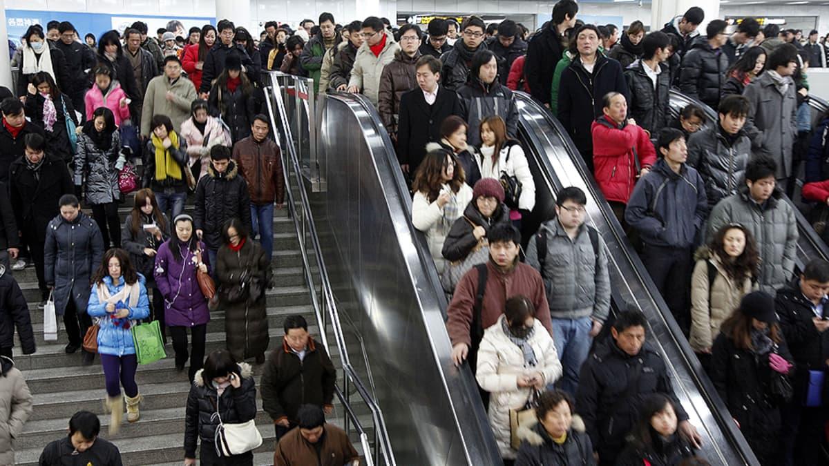 Työmatkalaisia metroasemalla Shanghaissa.