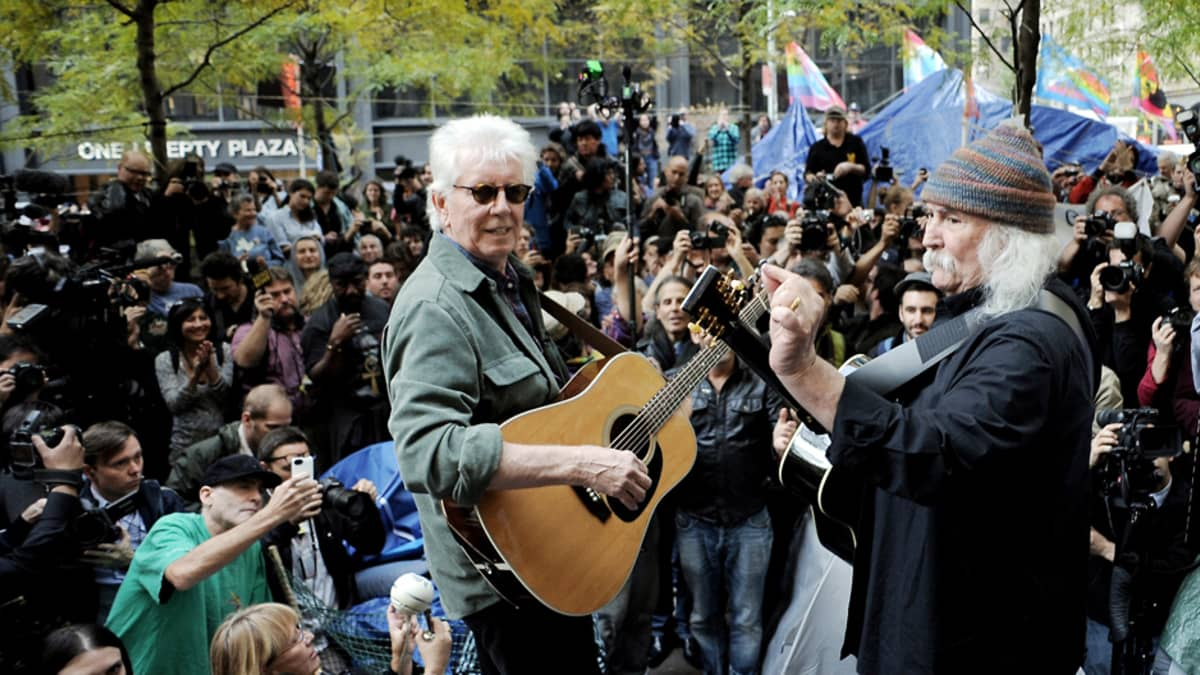 Muusikot esiintyvät kitaroineen, taustalla joukko katsojia ja mielenosoitusleiri.