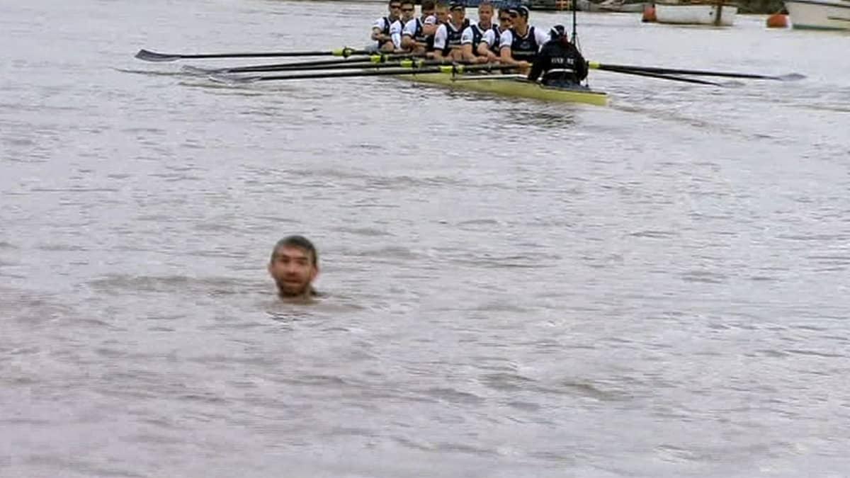 Cambridgen ja Oxfordin yliopistojen välisen soutukisan keskeyttänyt uimari Thames-joessa. Taustalla Cambridgen joukkueen vene.