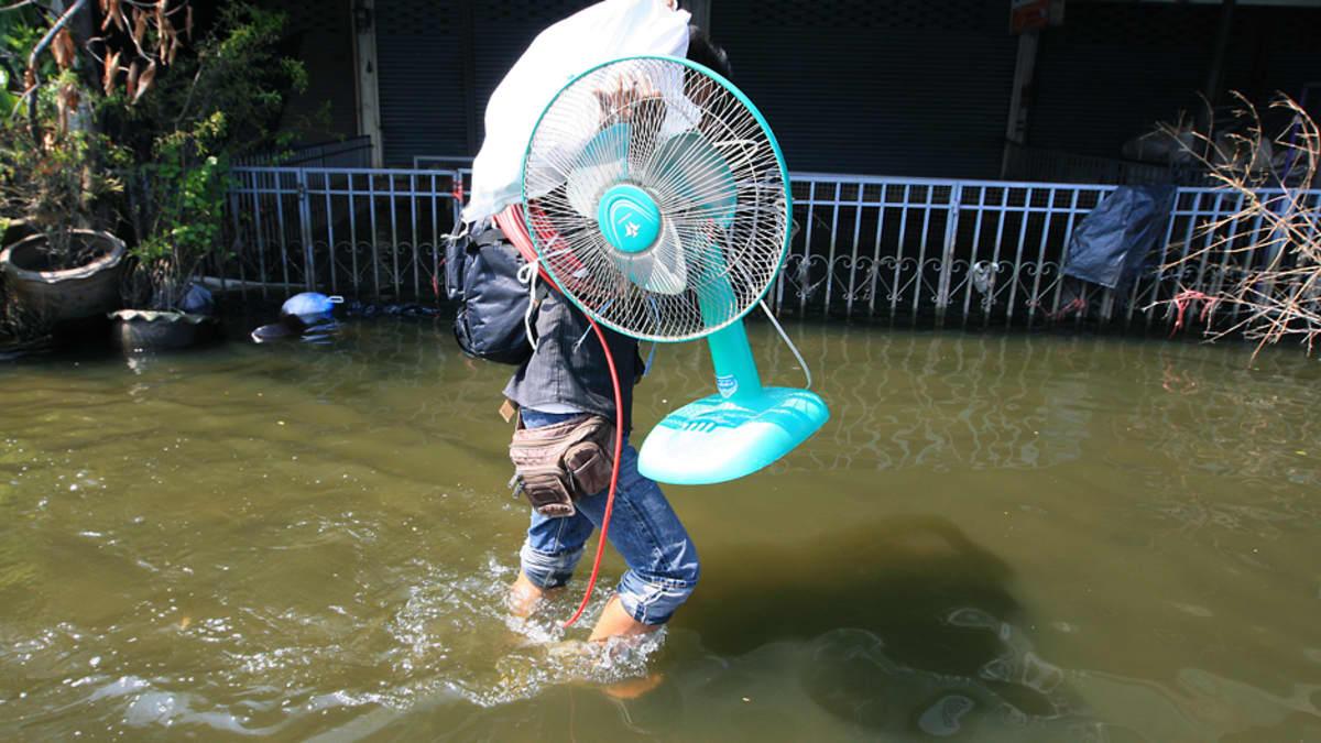 Nuori nainen kantaa isoa tuuletinta polviin ulottuvassa tulvavedessä Bangkokin lähiössä.