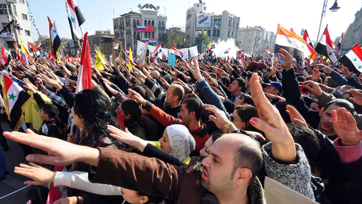 Presidentti Bashar al-Assadin puolesta aukiolle kokoontuneet mielenosoittajat ovat nostaneet oikean kätensä viistosti ilmaan.