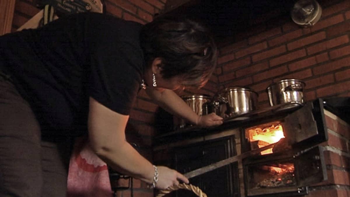 nainen kohentaa tulta uunissa