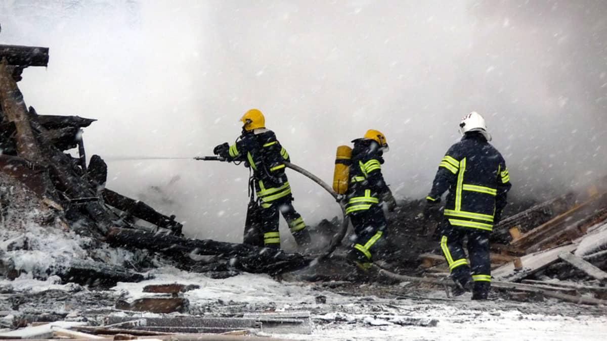Palomiehet sammuttavat savuavaa jätepuukasaa
