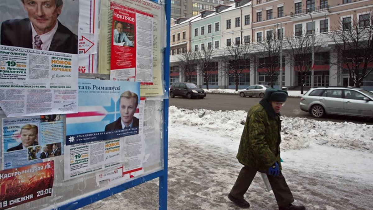 Valkovenäläinen mies ohittaa presidentinvaalimainostelineen Minskissä.