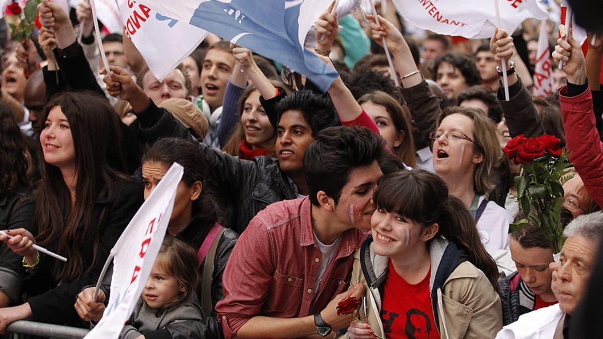 Francois Hollanden kannattajia sosialistien päämajan ulkopuolella Pariisissa vähän ennen toisen kierroksen tuloksen julkistamista.