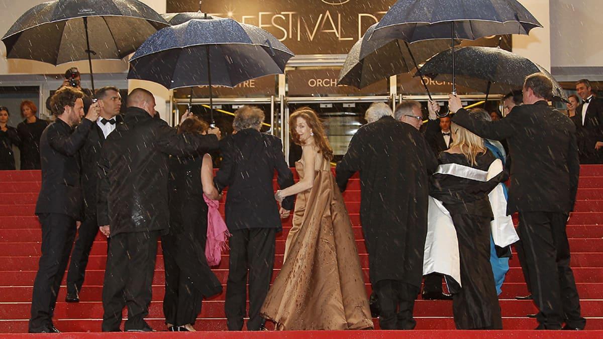 Ranskalainen näyttelijä Isabelle Huppert (kesk.) saapumassa seurueineen Amour-elokuvan näytökseen Cannesin filmifestivaaleilla.