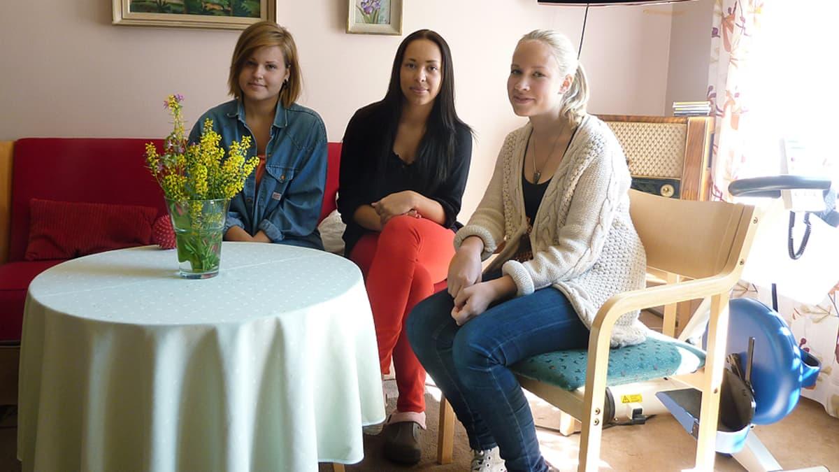 Kolme nuorta naista istumassa.