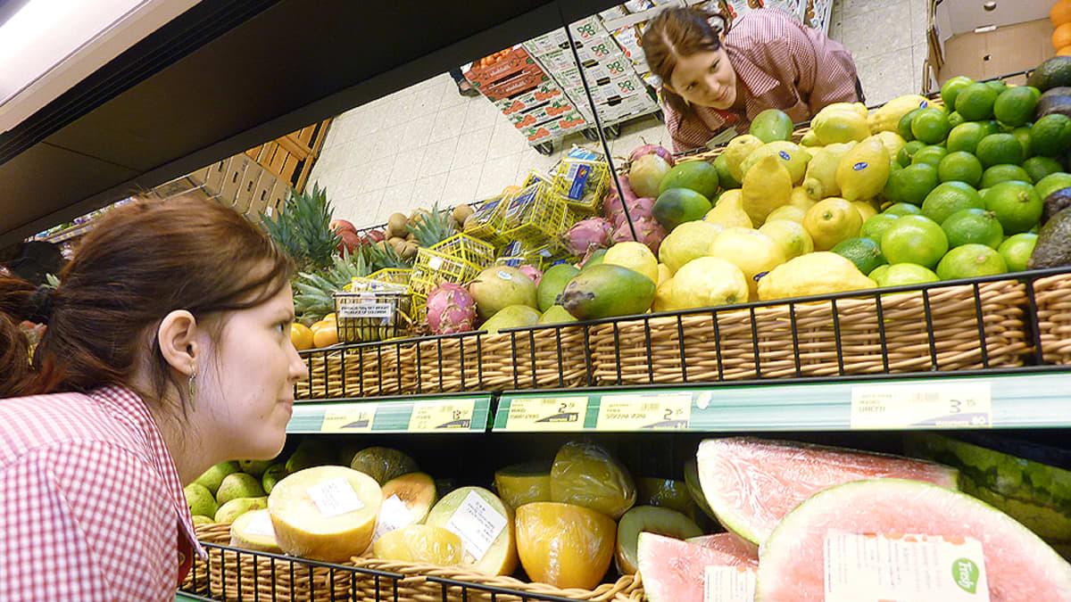Kaupan myyjä hedelmätiskin äärellä.