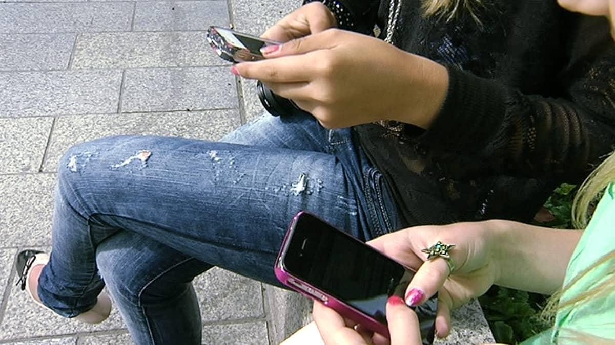Kaksi tyttöä näppäilemässä kännyköitään.