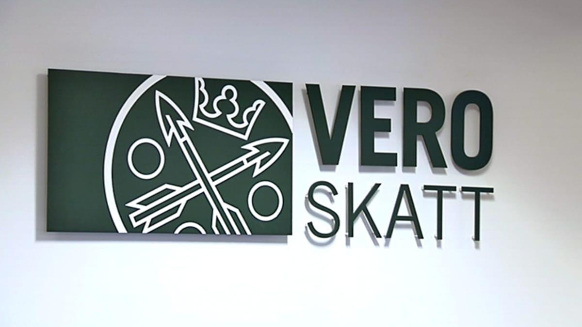 Vero- ja skatt-tekstit logosymbolin kanssa valkoisella seinällä. Tekstit ovat hieman irti seinästä, jolloin niiden alle muodostuu pienoinen varjo.