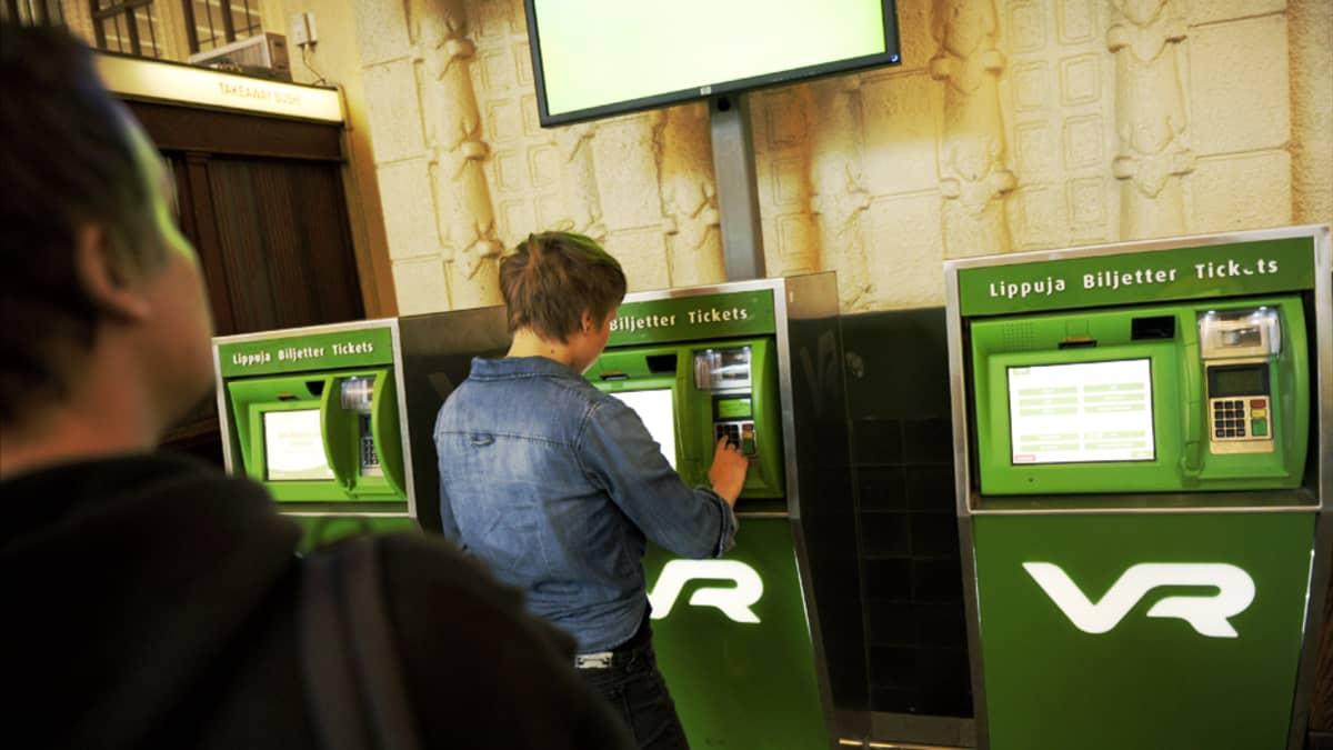 Asiakkaita VR:n lippuautomaatilla Helsingin rautatieasemalla.