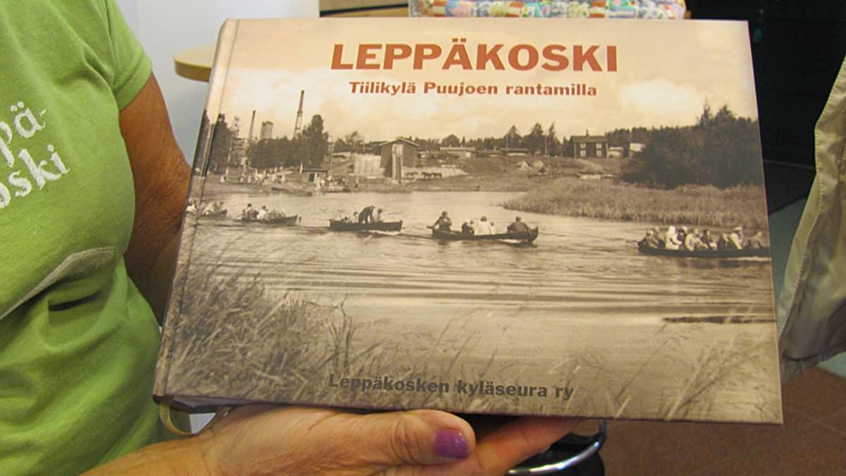 Leppäkosken kyläkirjan kansi: soutuveneet täynnä väkeä, takana tiilitehtaan piippu