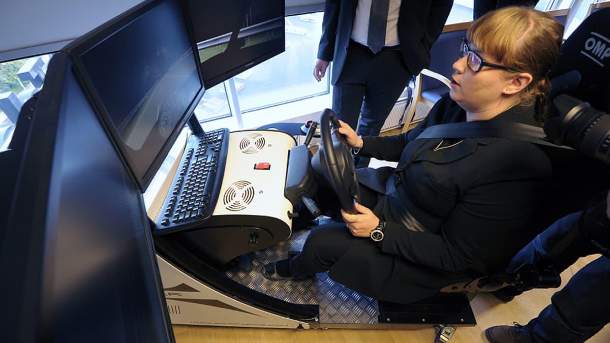 Liikenneministeri Merja Kyllönen ajaa simulaattoria.