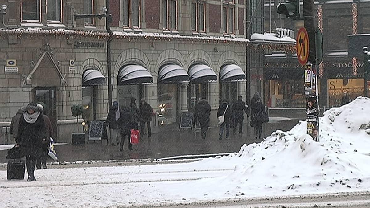 Ihmisiä lumisateessa Helsingin keskustassa.