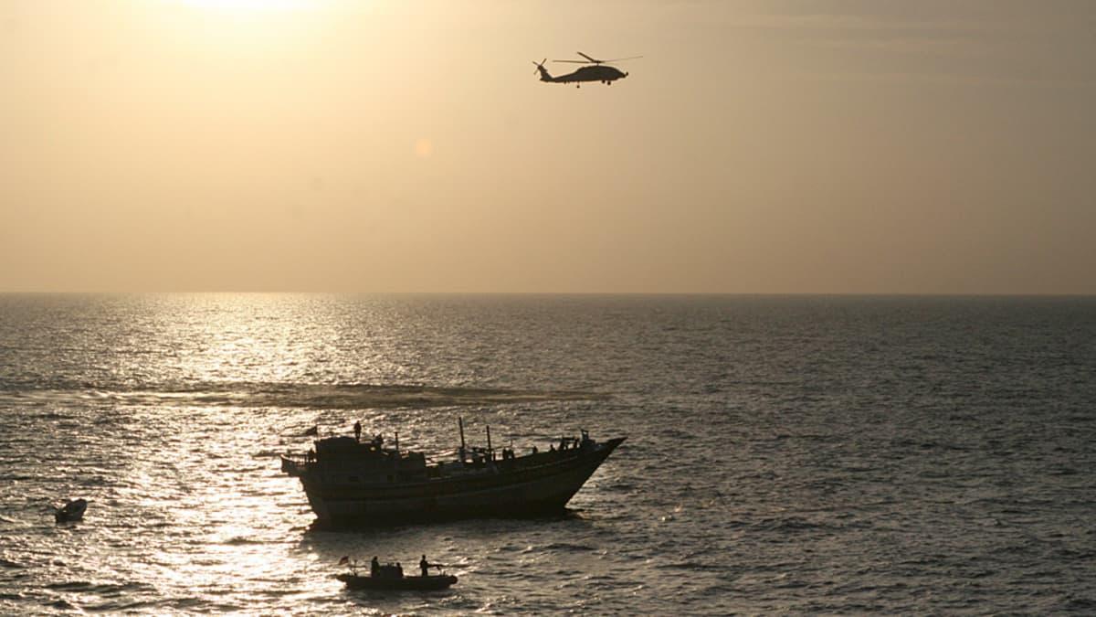 Laiva ja sen ympärillä moottoriveneitä sekä helikopteri ilmassa yläpuolella.