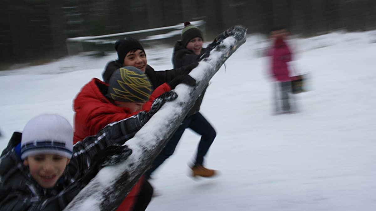 Venäläislapset työntävät jääkelkan puomia vauhdikkaasti