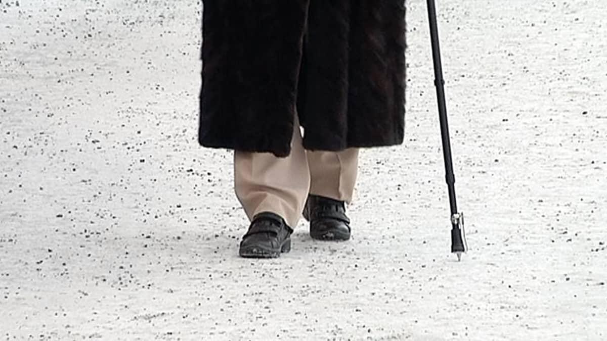 Vanhuksen jalat ja kävelykeppi hiekoitetulla jalkakäytävällä.