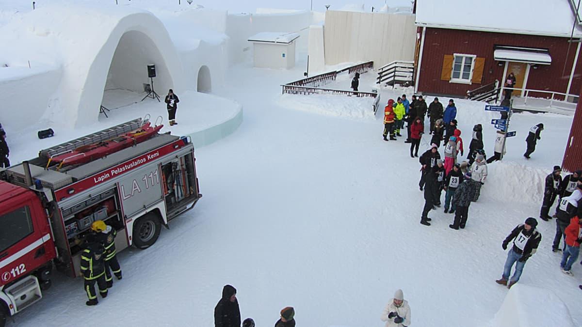 Paloauto ja ihmisiä lumilinnan pihalla