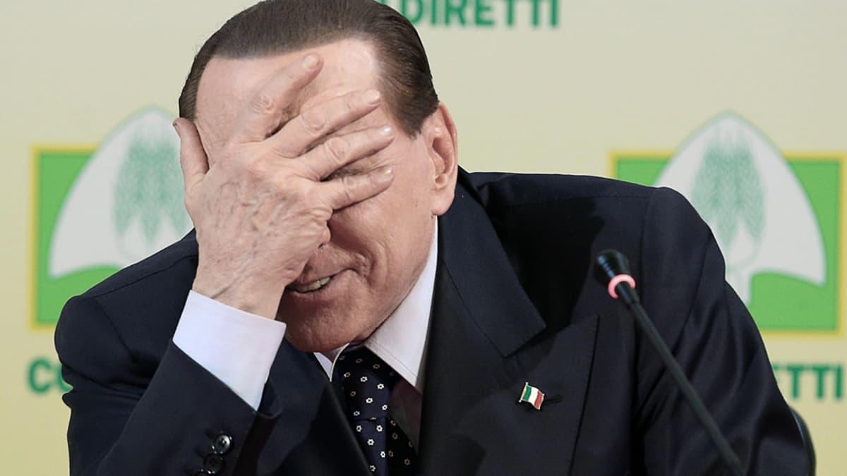 Silvio Berlusconi käsi naamallaan.
