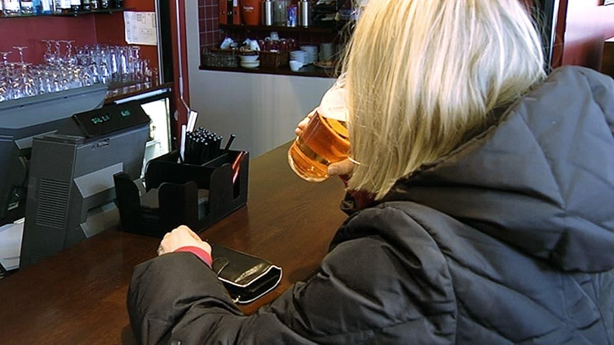 Nainen juo olutta baaritiskillä.