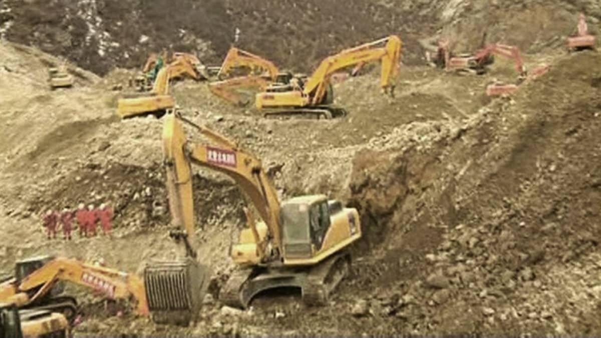 Lukuisia maankaivuukoneita työskentelee epätasaisessa soramaastossa.