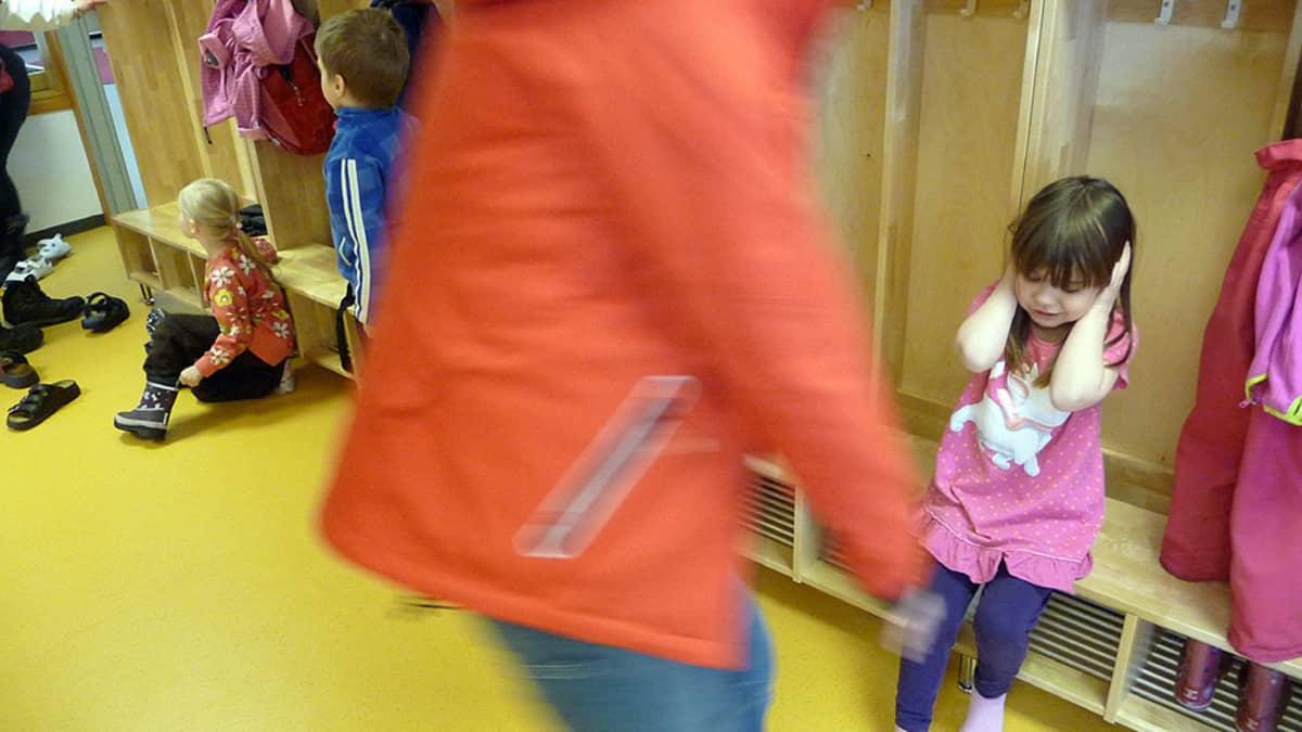 Putaan päiväkodin aulassa lapsia ja hoitajia pukeutumassa