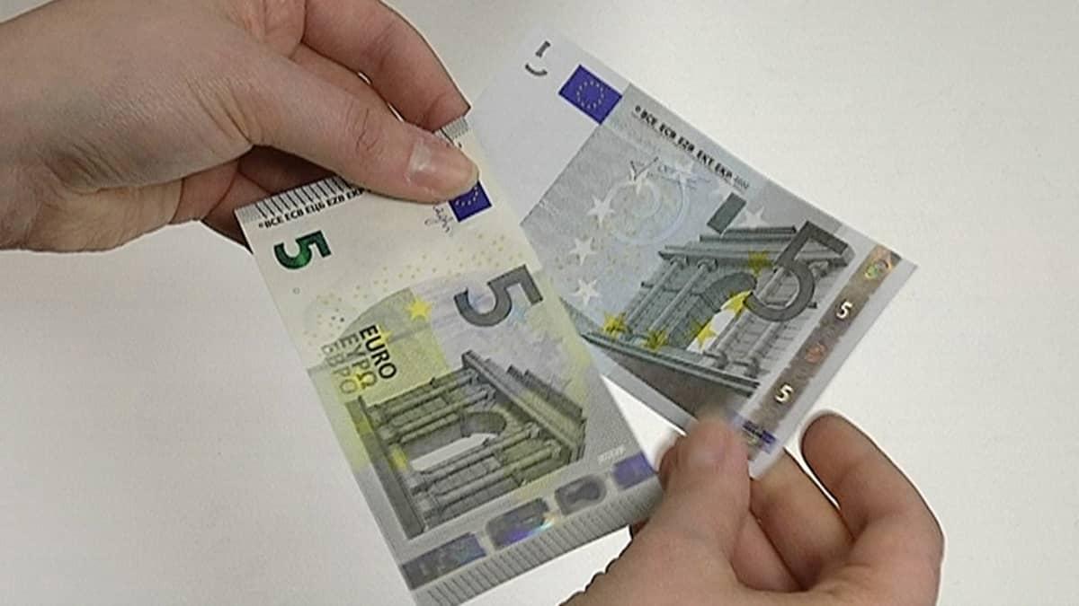 Henkilö pitelee uutta ja vanhaa viiden euron seteliä.