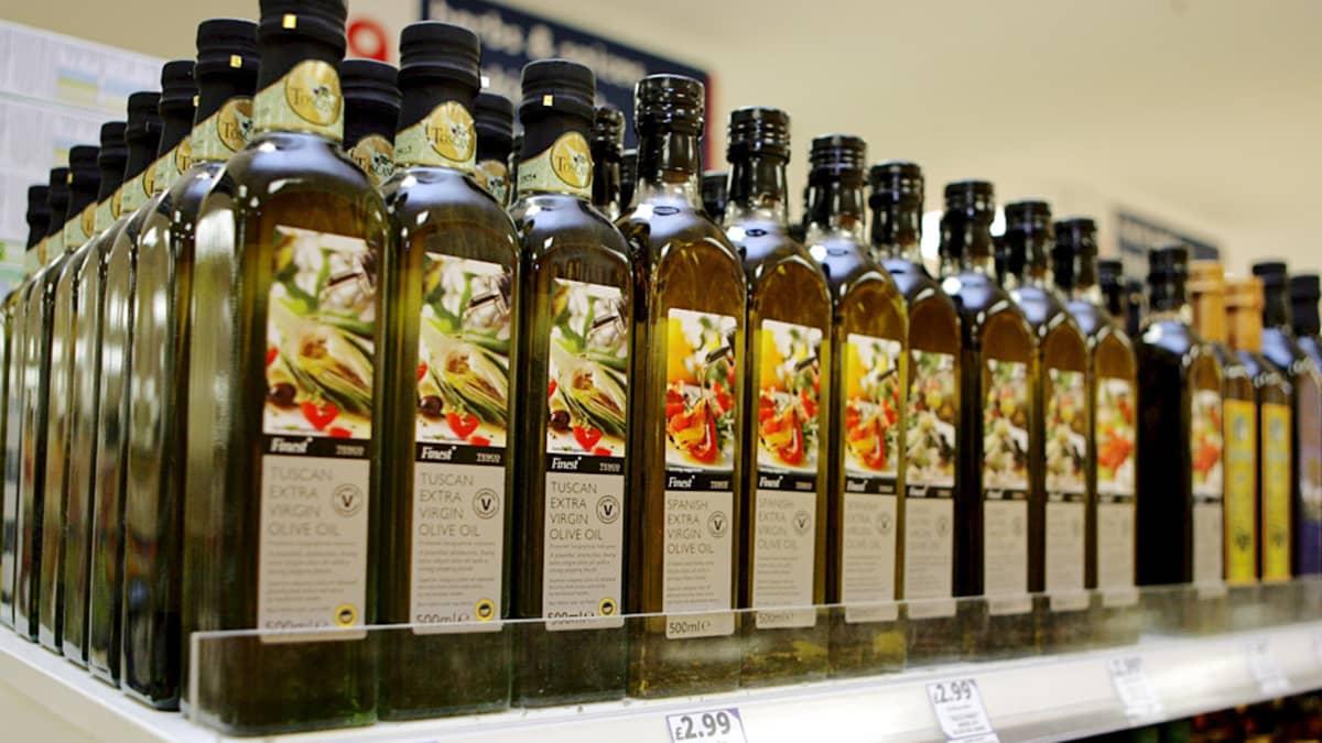 Oliiviöljypulloja rivissä kaupan hyllyllä.