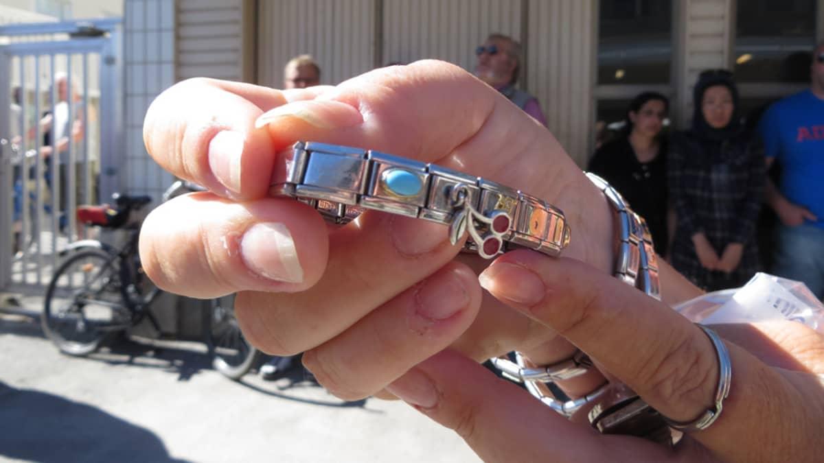 Rannekoru naisen käsissä. Nainen pitelee korua sormissaan.