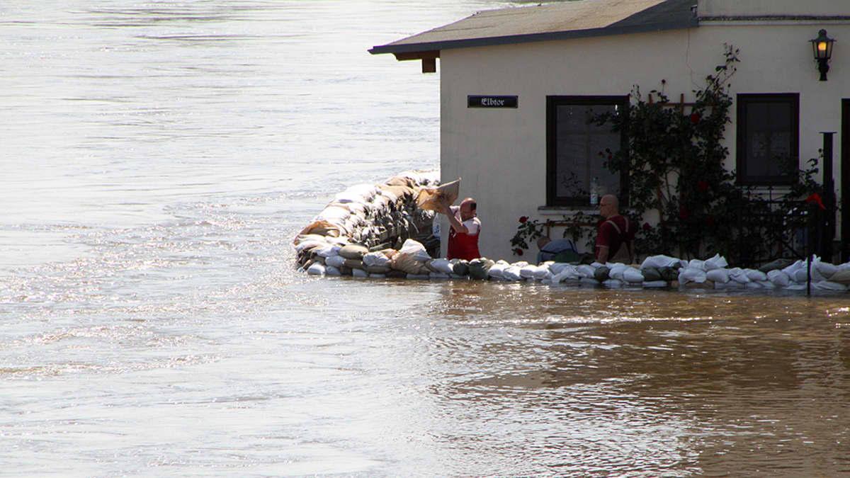 Ihmiset kasaavat hiekkasäkkejä tulvan saartaman talonsa ympärille.