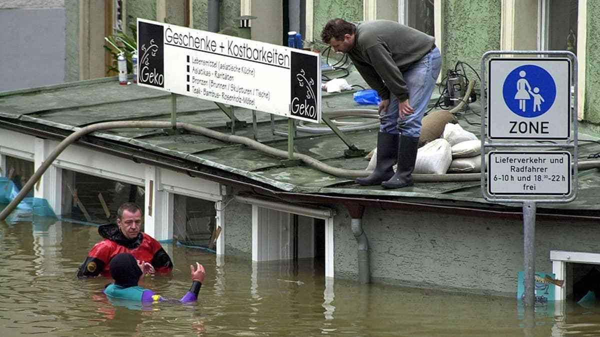 Pelastussukeltajat puhuvat tulvaa talon katolle paenneenmiehen kanssa.