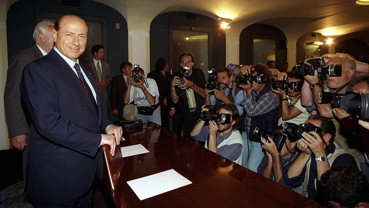 Silvio Berlusconi poseeraa kuvaajille lehdistötilaisuudessa.