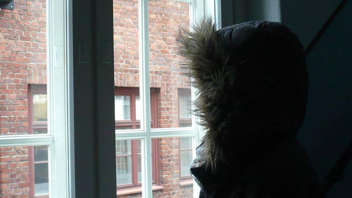 nuori huppu päässä ikkunan edessä