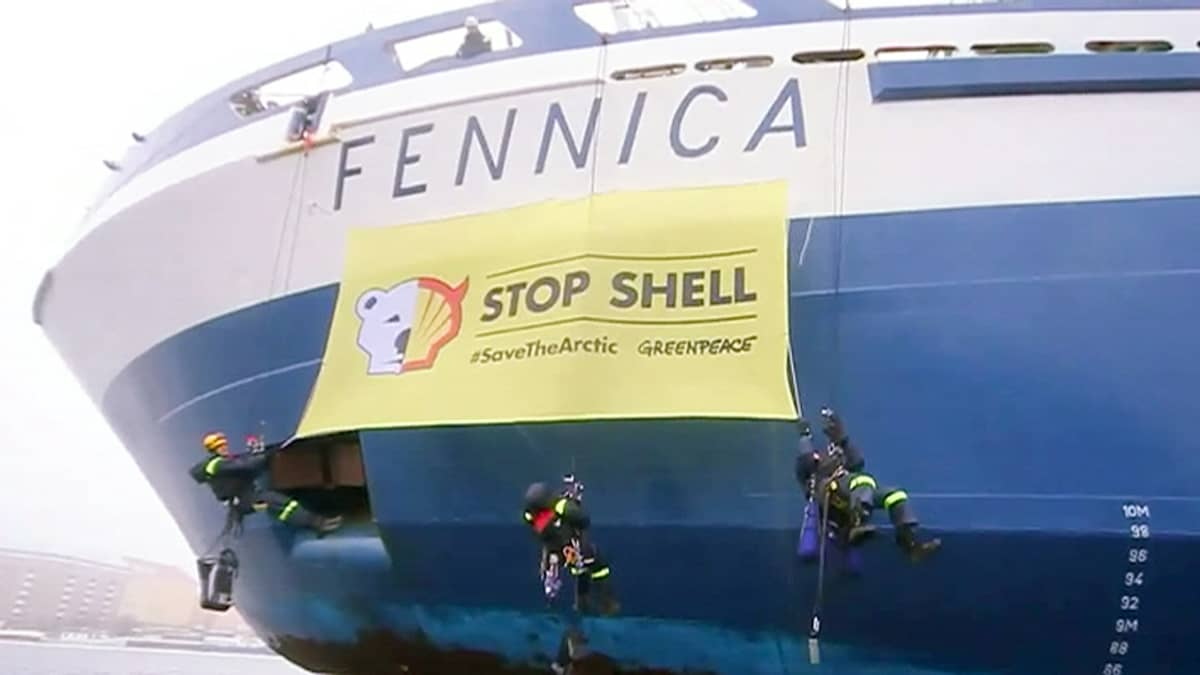 Greenpeacen aktivistit ripustamassa Shellin vastaista banderollia jäänmurtaja Fennican kylkeen Helsingin Katajanokalla.