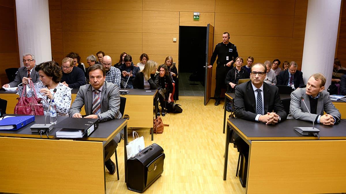 AKT:n yhteyspäällikkö Hilkka Ahde ja hänen asianajaja Mika Kivikoski ja AKT:n entinen puheenjohtaja Timo Räty ja hänen asianajaja Heikki Lampela Helsingin käräjäoikeuden oikeussalissa.