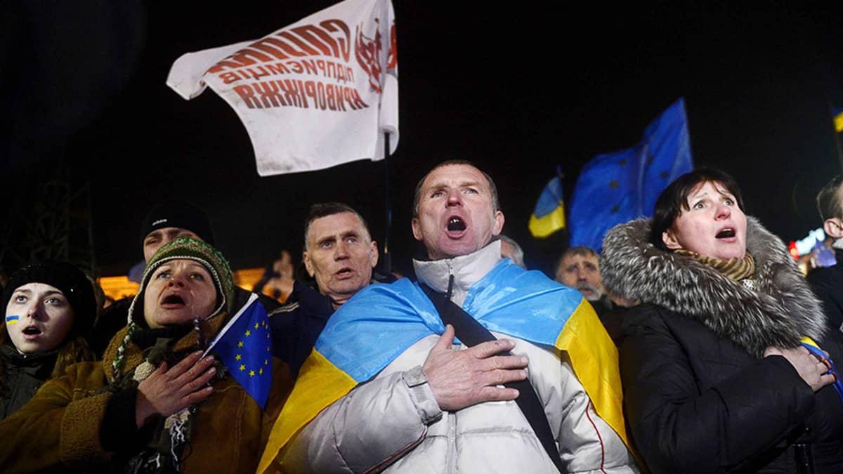 Ihmiset laulavat Ukrainan kansallislaulua Kiovassa osana mielenosoitusta.