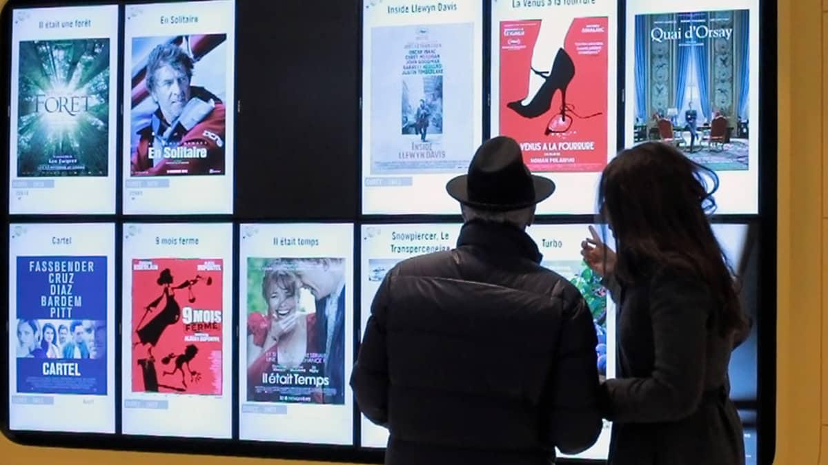 Mies ja nainen katselevat pariisilaisessa Pathé Beaugrenelle -elokuvateatterissa elokuvajulisteita.