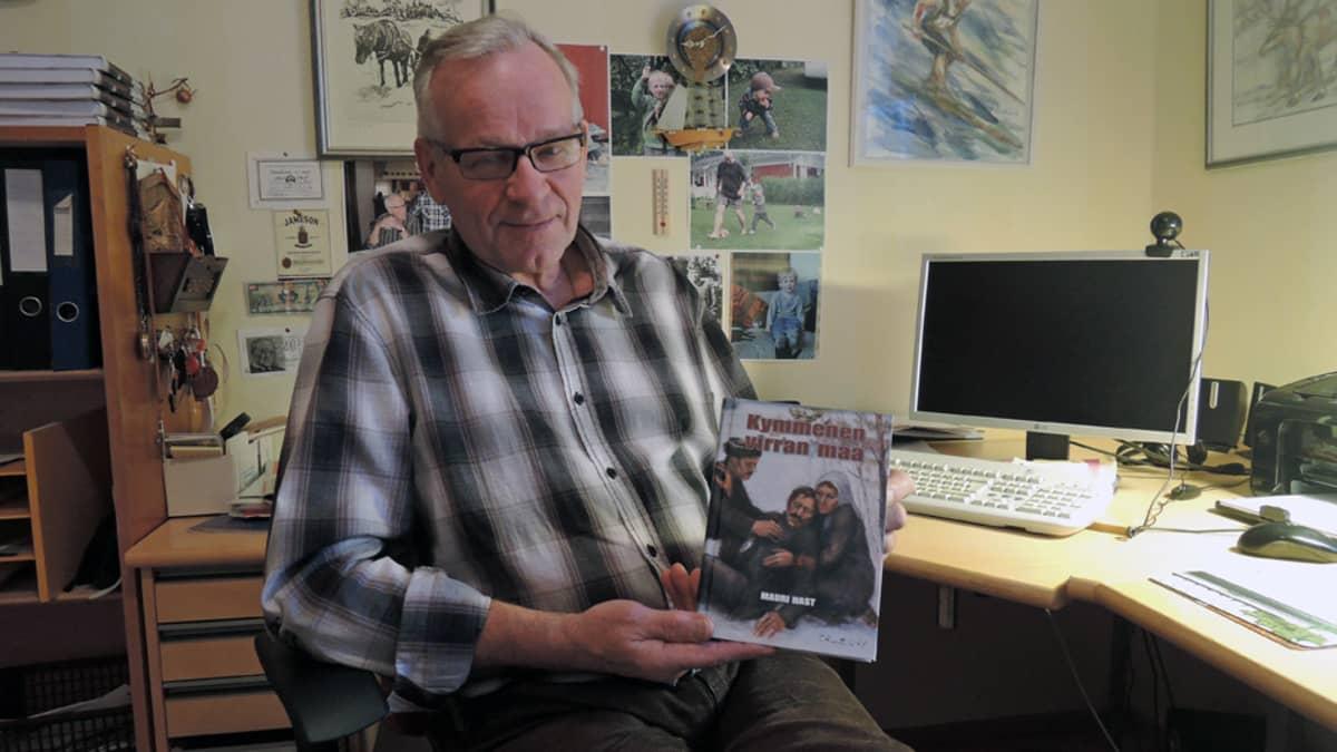 Kirjailija Mauri Hast pitää kädessään uutta kirjaansa Kymmenen virran maa.